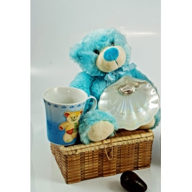 Blue children's trunk. Mug, teddy bear and nacre shell