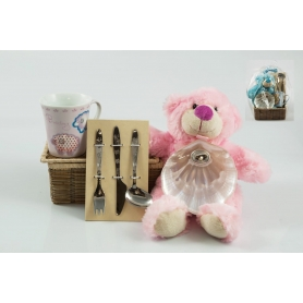 Pink children's basket. Mug, cutlery, shell and teddy bear